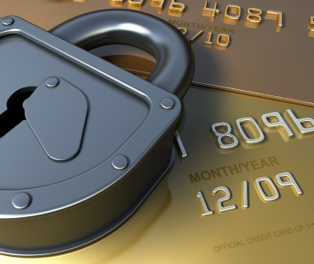 Image of a padlock laying on top of gold credit cards